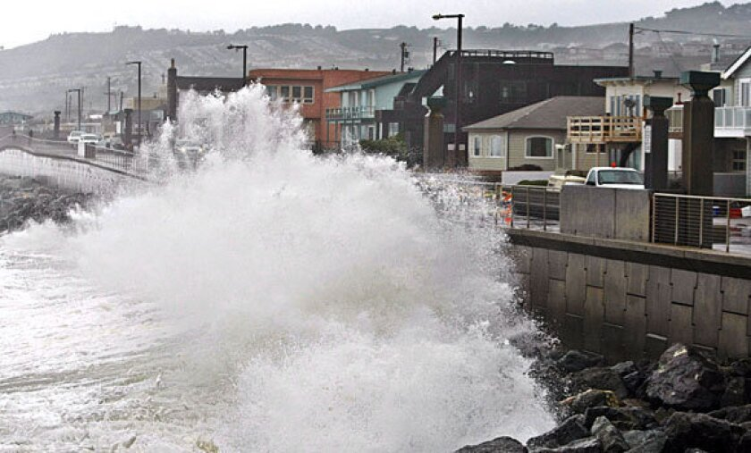 Waves pound a wall in Pacifica, Calif., during a January 2010 storm. A recent survey found that most Americans were no longer willing to accept a hands-off approach to continued coastal development that will get battered repeatedly by rising seas as the climate changes.