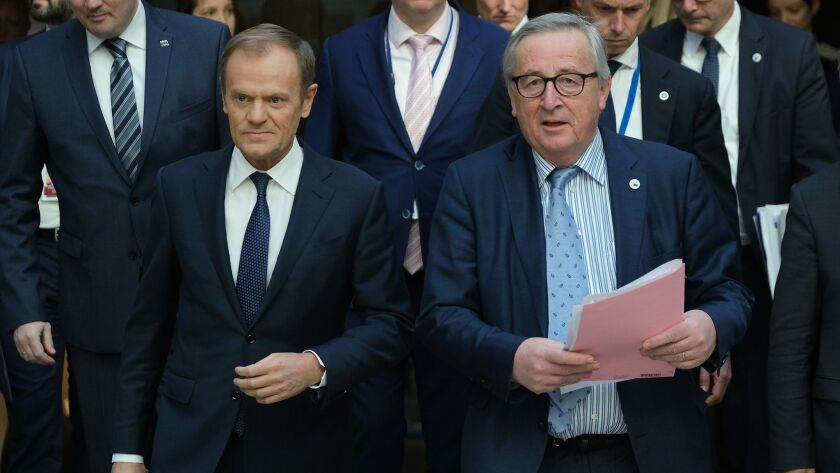 European Council President Donald Tusk, left, and European Commission President Jean-Claude Juncker arrive to speak to the media at the conclusion of a two-day EU summit March 22 in Brussels.