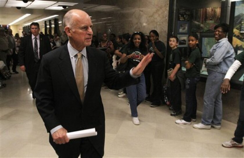 Gov. Jerry Brown waves to a tour group as he returns to his office after unveiling his revised state budget plan at a Capitol news conference in Sacramento, Calif., Monday, May 14, 2012. Brown said the budget shortfall swelled from $9.2 billion predicted in January to $16 billion, in part because t