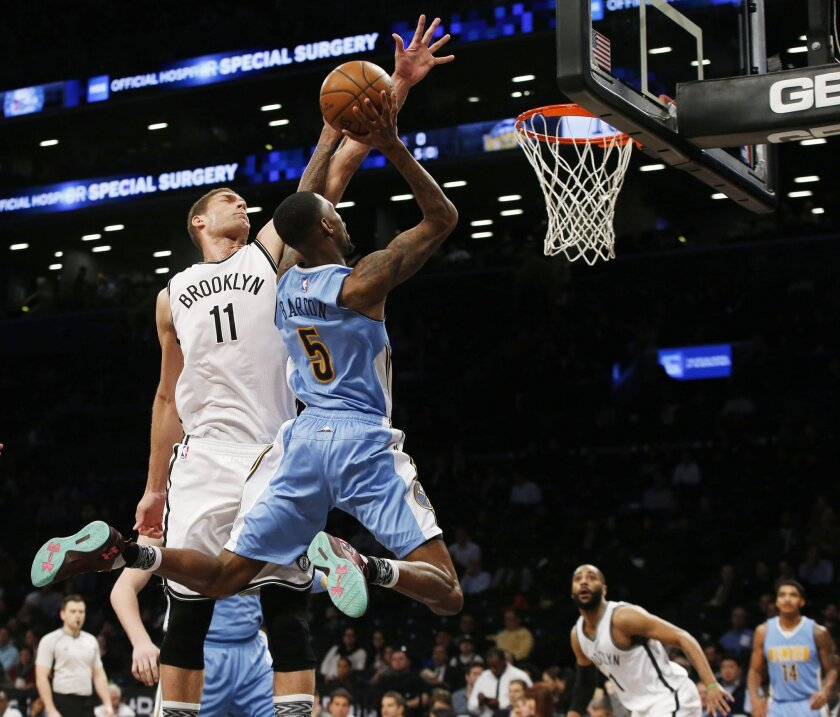 Brooklyn Nets center Brook Lopez (11) defends Denver Nuggets forward Will Barton (5) who goes up for a lay-up in the first half of an NBA basketball game, Monday, Feb. 8, 2016, in New York. (AP Photo/Kathy Willens)