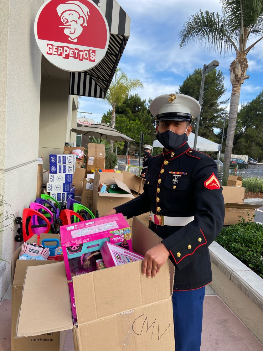 A Marine loads up Toys for Tots donations at Geppetto's in Del Mar Highlands Town Center.