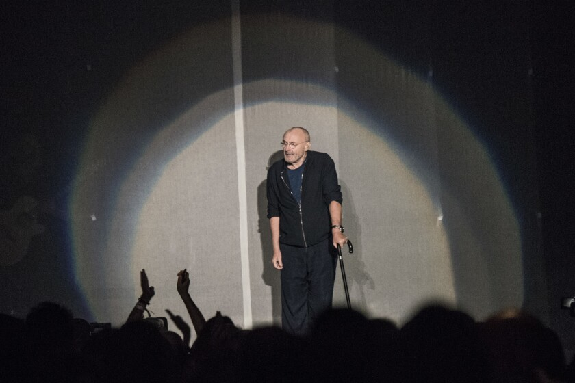 Phil Collins comes onstage assisted by a cane after having back surgery on October 28, 2018 at the F