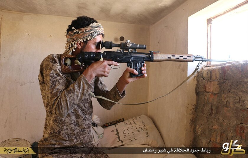 In this photo released on June 23, 2015, by a website of Islamic State militants, an Islamic State militant looks through the scope of his rifle in Kirkuk, northern Iraq. Though best known for its horrific brutalities _ from its grotesque killings of captives to enslavement of women _ the Islamic S