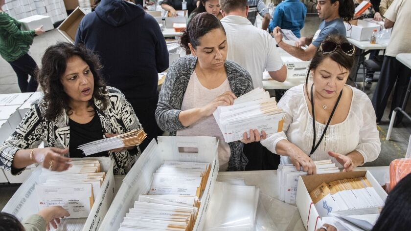 Employees of the Orange County Registrar of Voters sort through mail-in ballots on Wednesday, Nov. 7