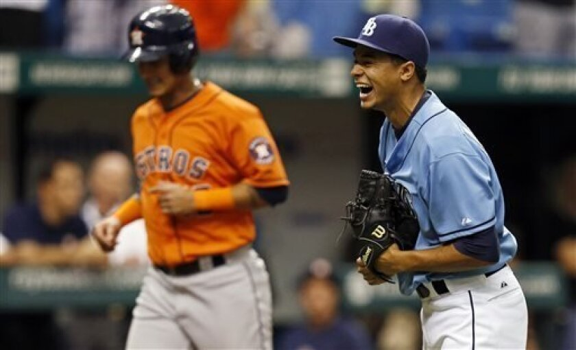 Tampa Bay Rays starting pitcher Chris Archer, right, celebrates the final out of the ninth inning as Houston Astros' Ronny Cedeno rounds the bases during a baseball game Sunday, July 14, 2013, in St. Petersburg, Fla. The Rays won 5-0. (AP Photo/Mike Carlson)