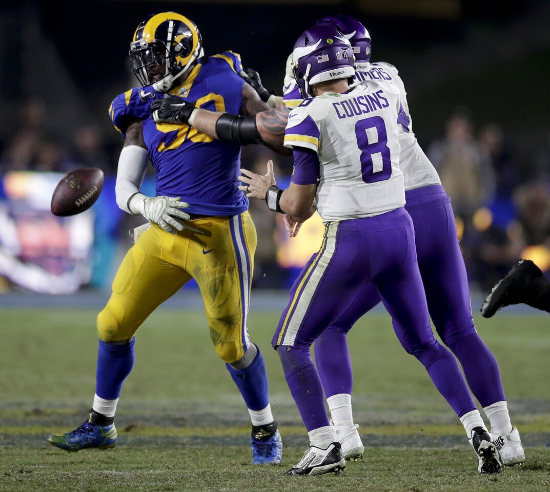 Los Angeles Rams defensive tackle Michael Brockers, left, forces a fumble by Minnesota Vikings quarterback Kirk Cousins during the second half in an NFL football game Thursday, Sept. 27, 2018, in Los Angeles. (AP Photo/Jae C. Hong)