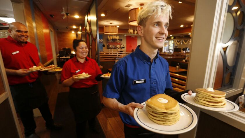 Servers carry plates of pancakes at an IHOP restaurant. The chain has to agreed to scrap its policy against worker poaching among franchises.