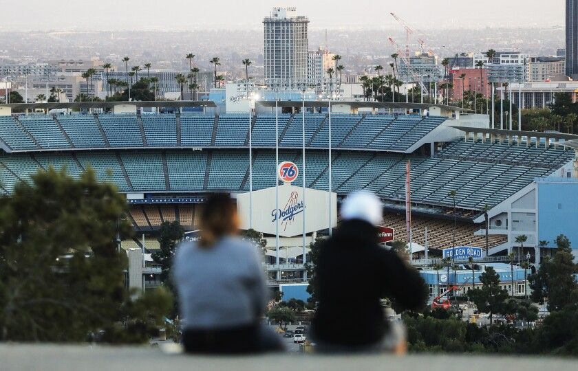 People sit on a hill overlooking Dodger Stadium on what was supposed to be Major League Baseball's opening day on March 26.