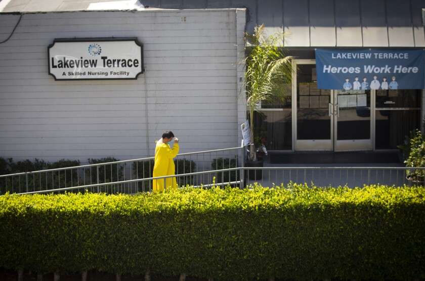 A man wearing an isolation gown walks toward the entrance of Lakeview Terrace nursing home.
