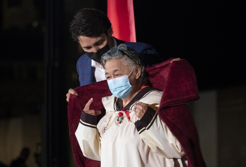 Canadian Prime Minister Justin Trudeau wraps residential school survivor and Inuk senior elder Levinia Brown in a blanket to keep her warm during a ceremony on Parliament Hill on the eve of the first National Day of Truth and Reconciliation, Wednesday, Sept. 29, 2021 in Ottawa, Ontario. (Adrian Wyld/The Canadian Press via AP)