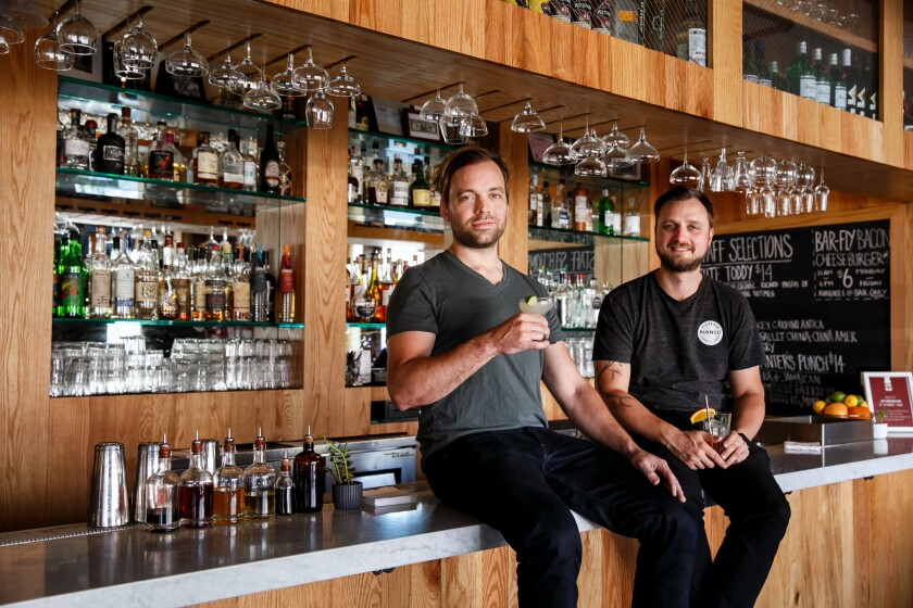 Salt's Cure chefs Chris Phelps, left, and Zak Walters perch atop the bar at their restaurant's new location on Highland.