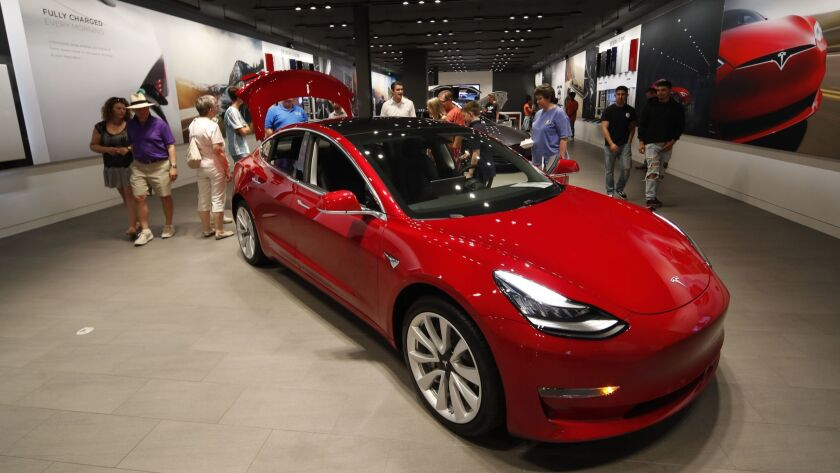 Prospective customers talk with sales associates as a Model 3 sits on display in a Tesla showroom in Denver in July.
