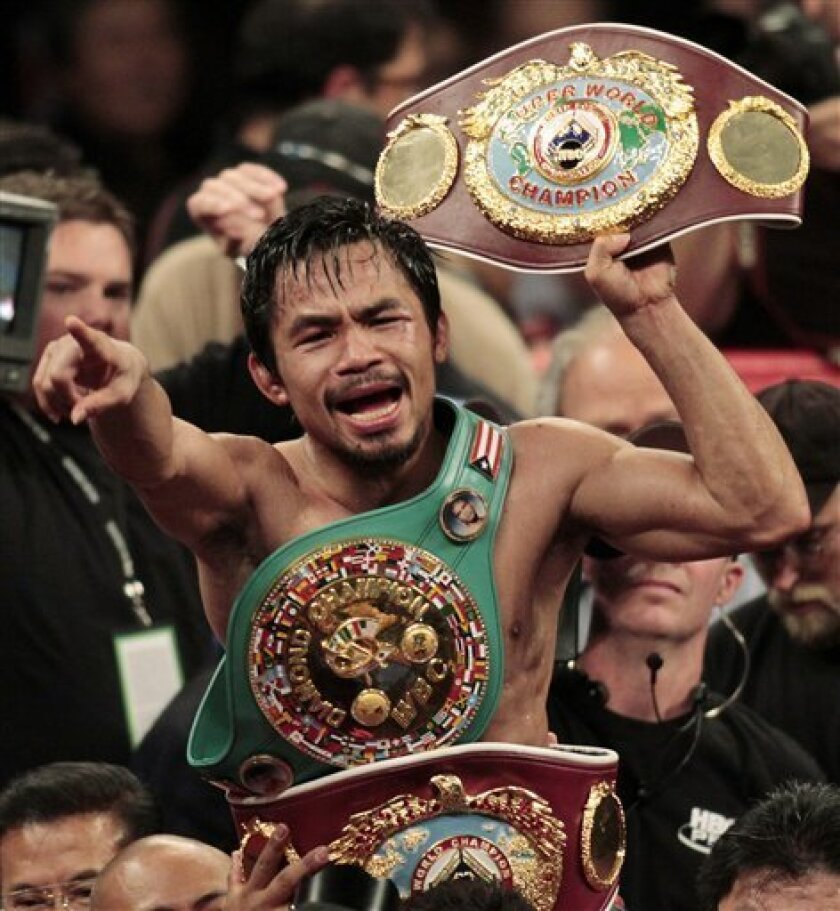 FILE - Manny Pacquiao, of the Philippines, holds the championship belt at the finish of his WBO welterweight boxing title fight against Miguel Cotto, of Puerto Rico, in this Nov. 14, 2009 file photo, in Las Vegas. Pacquiao won the fight by TKO in the 12th round. Pacquiao did what no fighter has done before--win a belt in seven weight classes. (AP Photo/Isaac Brekken, File)
