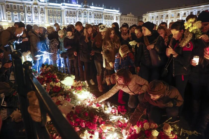 Un grupo de personas enciende velas durante el día de luto oficial por las víctimas de un accidente de avión, en su mayoría rusos, en la península egipcia del Sinaí, en la plaza del palacio Dvortsovaya, en San Petersburgo, Rusia, el 1 de noviembre de 2015. (Foto AP/Dmitry Lovetsky)