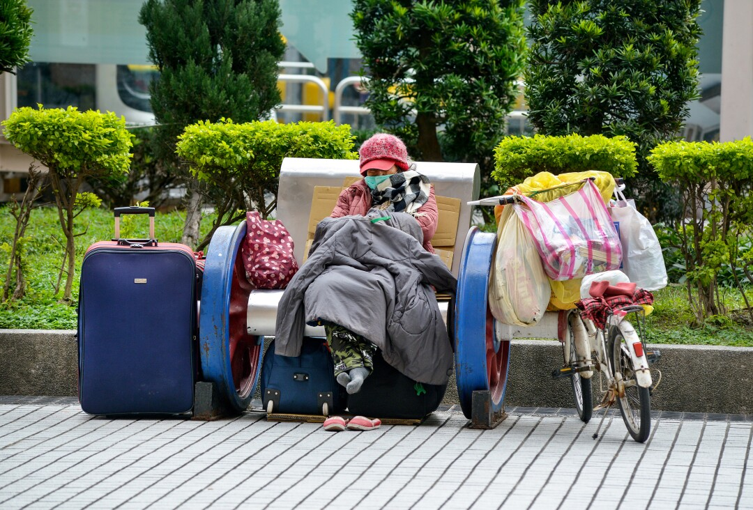 A homeless woman with her belongings at the main rail station in Taipei, Taiwan.