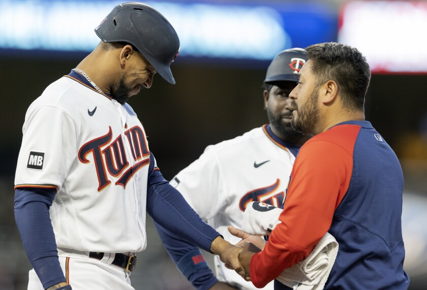 Minnesota Twins' Byron Buxton is looked at by trainer Michael Salazar after being hit by a pitch in the fourth inning of a baseball game against the Cincinnati Reds, Monday, June 21, 2021, in Minneapolis. (Carlos Gonzalez/Star Tribune via AP)