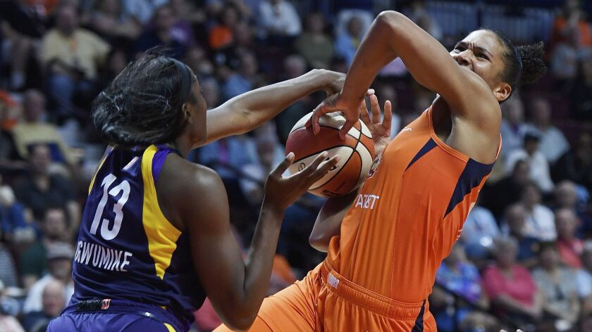 Los Angeles Sparks center Chiney Ogwumike, left, blocks a shot attempt by Connecticut Sun forward Al
