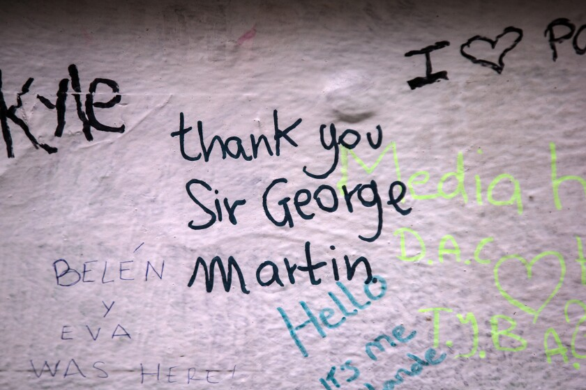 A message in tribute to Beatles producer George Martin is seen on the wall of Abbey Road Studios on Wednesday in London. Martin, who produced the Beatles, passed away Tuesday at 90.