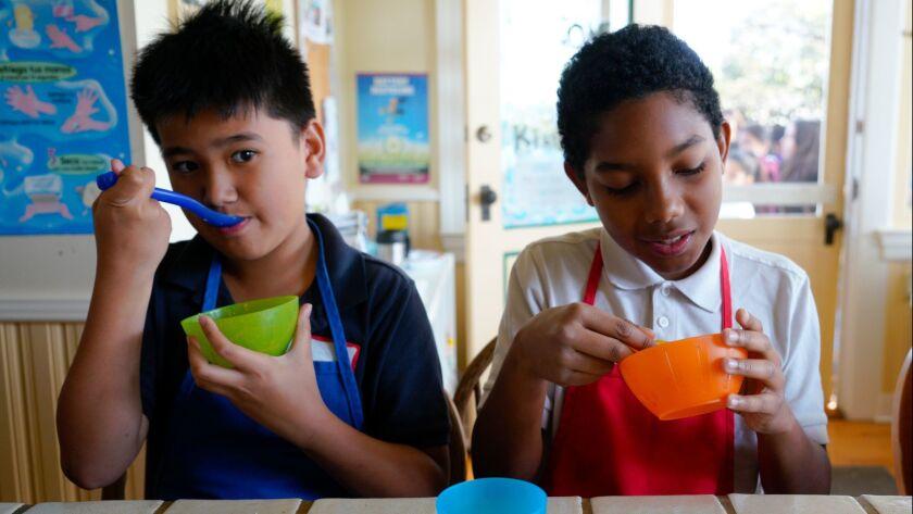 Carlos Villasenor (l) and Izaiah Lorias (r) sample a cauliflower dish that they helped prepare at th