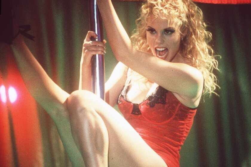 A woman clad in red lingerie holds a stripper pole with great ferocity