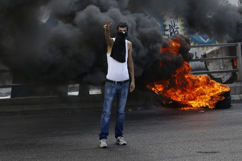 An anti-government protester makes victory sign next to tires that were set on fire to block a road during a demonstration, in Beirut, Lebanon, Sunday, Sept. 29, 2019. Hundreds of Lebanese are protesting an economic crisis that has worsened over the past two weeks, with a drop in the local currency for the first time in more than two decades. (AP Photo/Bilal Hussein)