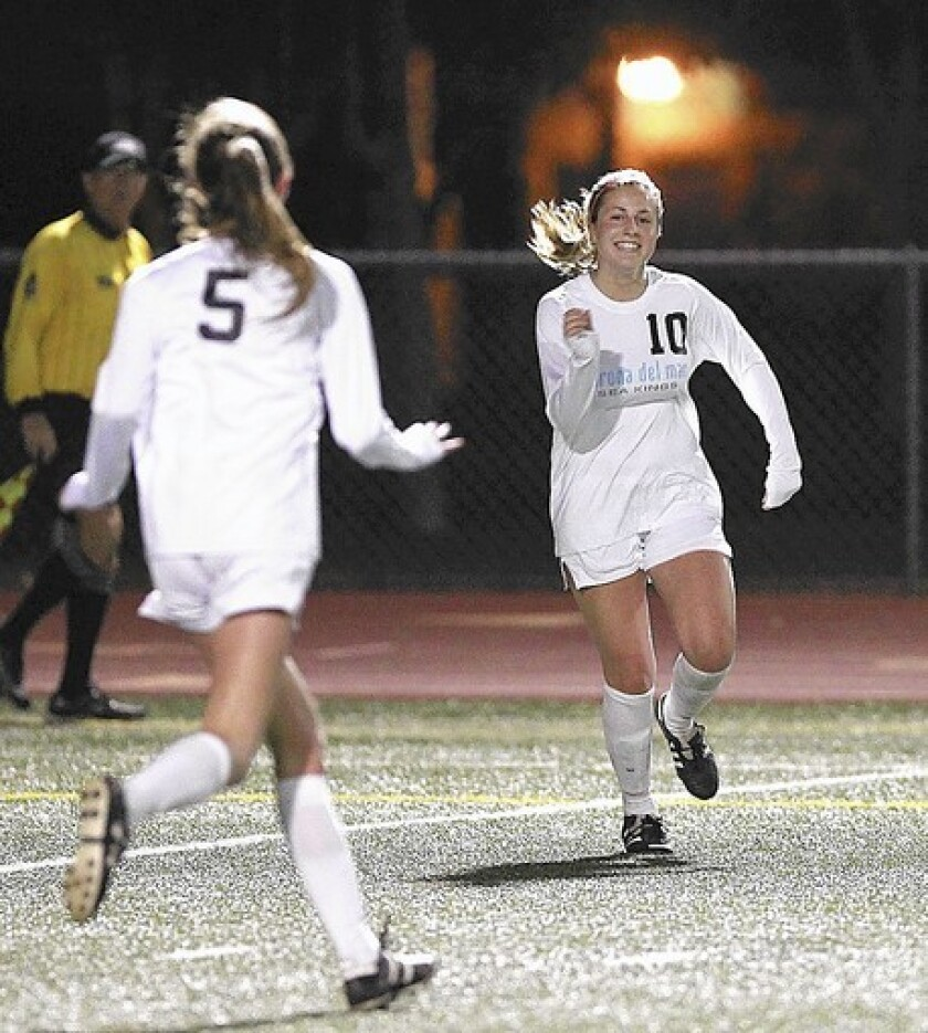 Corona del Mar High's Shelby Brown (10) celebrates after a goal with teammate Elise Roche (5) during a match against Beckman in Pacific Coast League action at Jim Scott Stadium on Tuesday.
