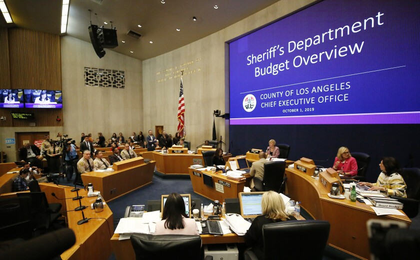 Los Angeles County Sheriff Alex Villanueva, at left, listens as members of the Los Angeles County Board of Supervisors discusses the Sheriff's Department's $63-million budget deficit.