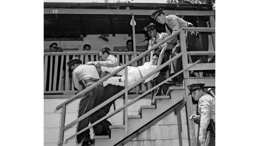 May 8, 1959: Aurora Vargas is carried by Los Angeles County sheriff's deputies during eviction from a house in Chavez Ravine. The photo was taken by Los Angeles Mirror-News photographer Hugh Arnott.