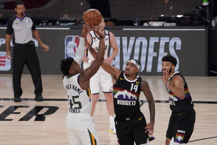 Utah's Donovan Mitchell attempts to shoot over Denver's Gary Harris.