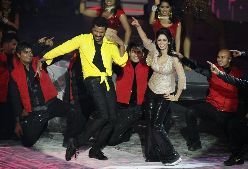 FILE - This July 6, 2013 file photo shows Bollywood actors Sridevi and Prabhu Deva, left in yellow, performing during the International Indian Film Academy (IIFA) awards in Macau. The IIFA is holding its annual awards ceremony in Tampa this week. The city is an unusual choice for the awards extravaganza, but tourism officials hope it will be an economic boon to Tampa, which has hosted four Super Bowls and the Republican National Convention. (AP Photo/Kin Cheung, File)