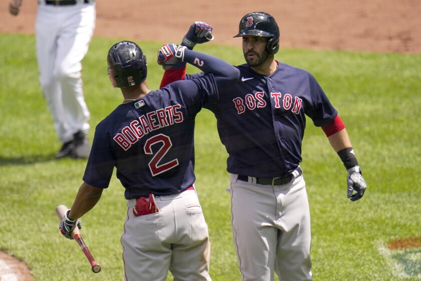 Boston Red Sox's J.D. Martinez, right, is greeted near home plate by Xander Bogaerts after hitting a solo home run off Baltimore Orioles starting pitcher Jorge Lopez during the third inning of a baseball game, Sunday, April 11, 2021, in Baltimore. (AP Photo/Julio Cortez)