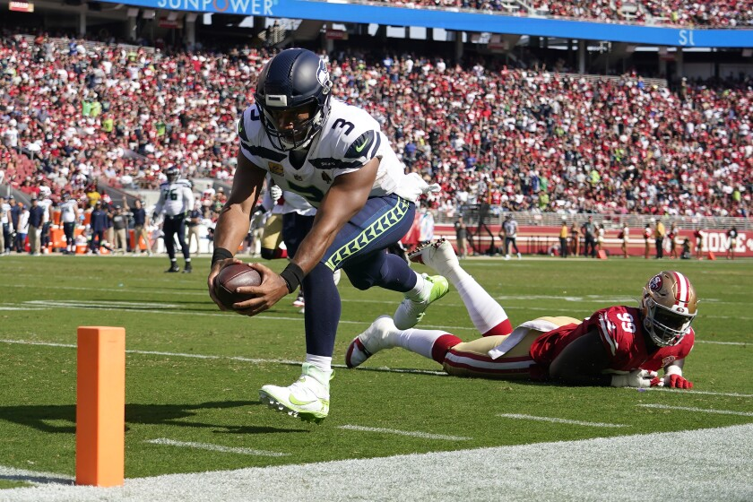 Seattle Seahawks quarterback Russell Wilson (3) runs for a touchdown past San Francisco 49ers defensive tackle Javon Kinlaw (99) during the second half of an NFL football game in Santa Clara, Calif., Sunday, Oct. 3, 2021. (AP Photo/Tony Avelar)