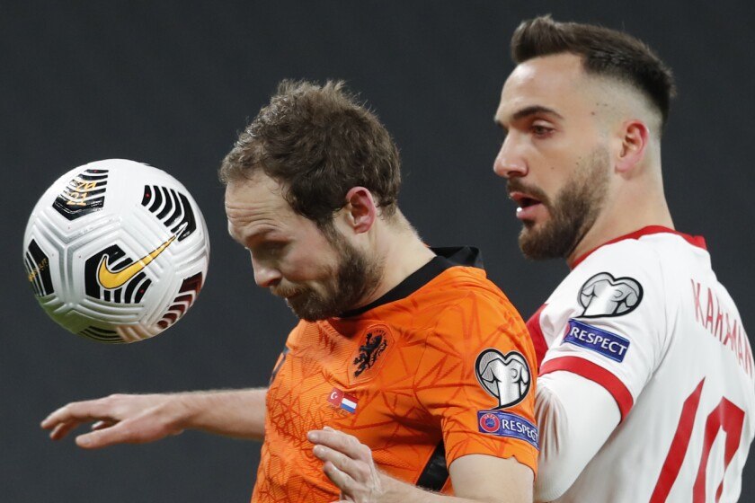 Netherlands' Daley Blind, left, is challenged by Turkey's Kenan Karaman during the World Cup 2022 group G qualifying soccer match between Turkey and Netherlands at the Ataturk Olimpiyat Stadium in Istanbul, Turkey, Wednesday, March 24, 2021. (Murad Sezer/Pool Photo via AP)