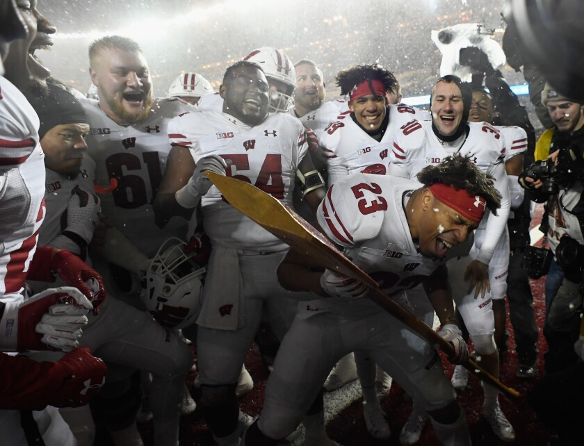 Wisconsin's Jonathan Taylor celebrates with the Paul Bunyan Axe trophy.
