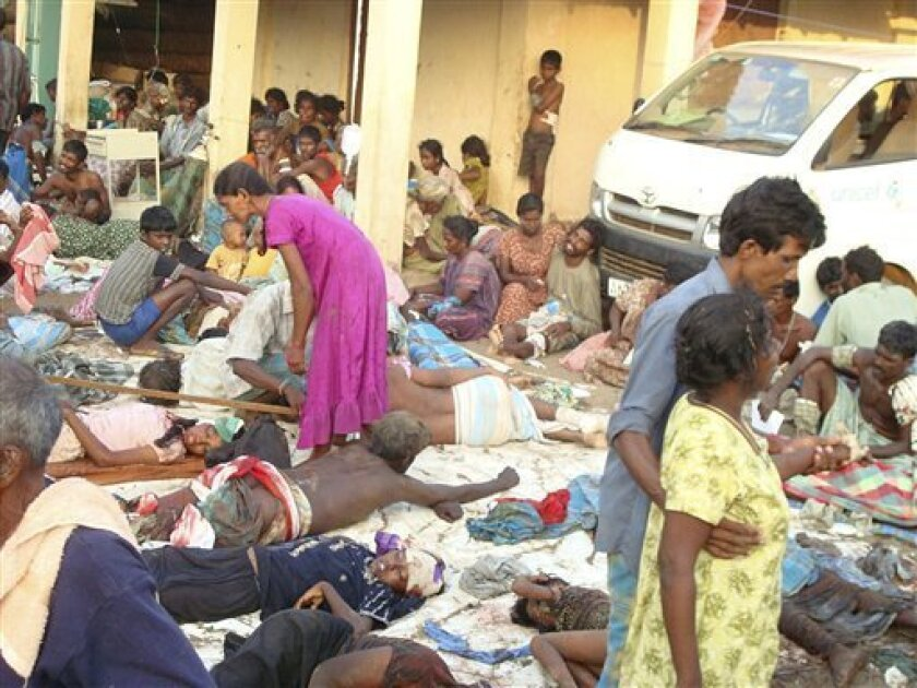 Sri Lankan ethnic Tamil victims of a shell attack wait outside a makeshift hospital in the Tiger-controlled No Fire Zone in Mullivaaykaal, Sri Lanka, Sunday, May 10, 2009. An all-night artillery barrage in Sri Lanka's war zone killed at least 378 civilians and forced thousands to flee to makeshift shelters along the beach, a government doctor said Sunday. The army and Tamil Tiger rebels blamed each other for the barrage, which the doctor said left at least 1,100 people wounded. He said it was the bloodiest day he had seen in months of fighting. (AP Photo)