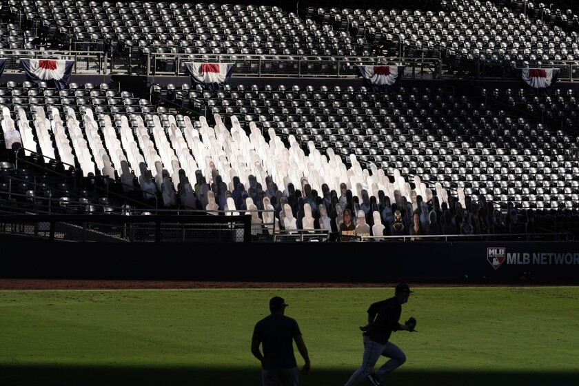 Sunlight reflects off fan cutouts in the seats at Petco Park during the ALCS.