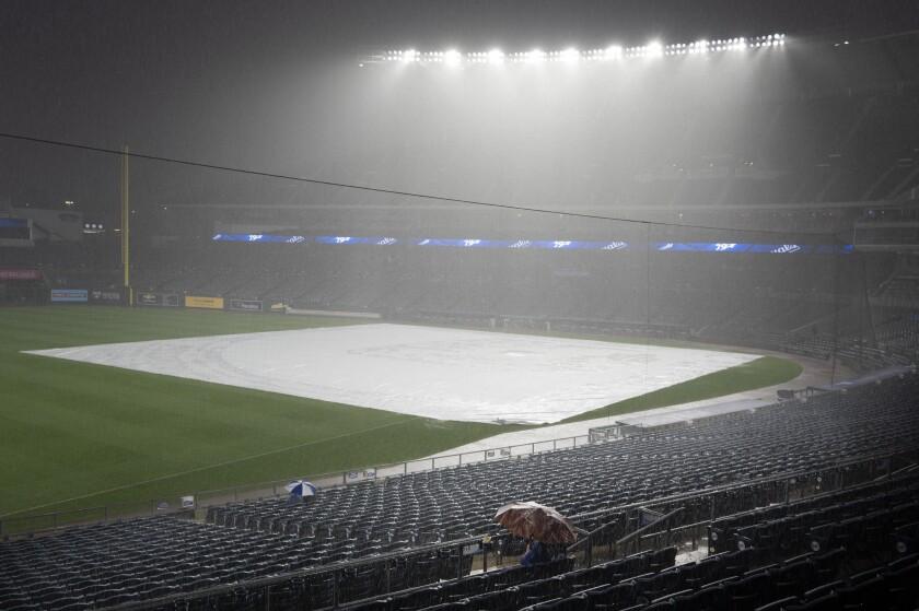 En foto del 3 de septiembre del 2021 algunos aficionados se sientan en el Estadio Kauffman después de que la lluvia obligó a atrasar el juego entre los Reales de Kansas City y los Medias Blancas de Chicago. El martes 14 de septiembre del 2021, cuando les quedan 10 años a su contrato con el estadio, los Reales evalúan sus opciones a futuro. (AP Photo/Reed Hoffmann)