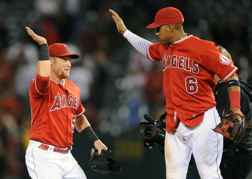 June 14, 2016; Anaheim, CA, USA; Los Angeles Angels right fielder Kole Calhoun (56) and third baseman Yunel Escobar (6) celebrate the 5-4 victory against Minnesota Twins at Angel Stadium of Anaheim. Mandatory Credit: Gary A. Vasquez-USA TODAY Sports ** Usable by SD ONLY **