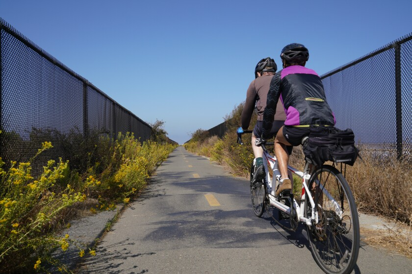 Two cyclists ride a tandem bike through a section of the Bayshore Bikeway connecting Chula Vista to Imperial Beach.