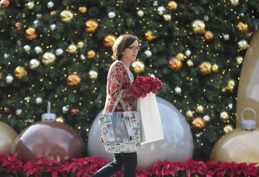 Jill Drew walks past the Christmas tree as she exits the Westfield UTC shopping mall after buying Christmas decorations and gifts in La Jolla on Thursday.
