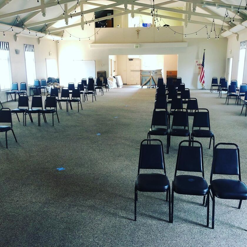 A room at St. Charles Borromeo is set for overflow seating, with rows of chairs spaced at least six feet apart.