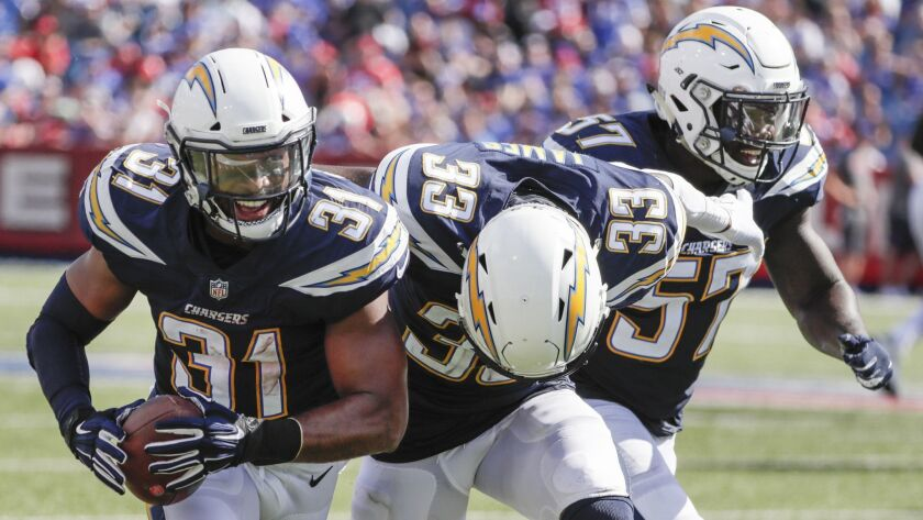 Chargers safety Adrian Phillips (left) celebrates an interception with teammates Derwin James (center) and Jatavis Brown.