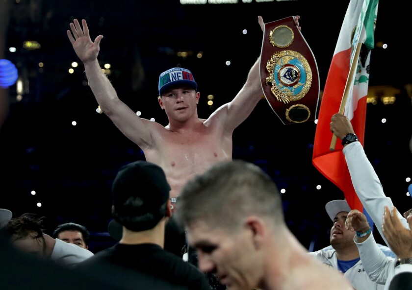 Canelo Alvarez celebrates after knocking out Liam Smith, lower middle, during their WBO junior-middleweight bout at AT&T Stadium in Arlington, Texas, on Sept. 17, 2016.