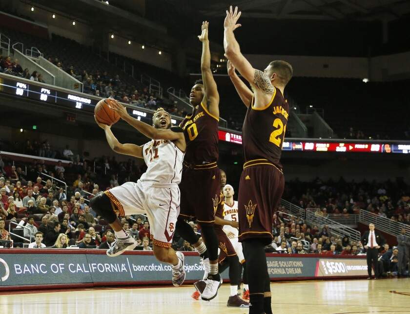 USC guard Jordan McLaughlin (11) drives to the basket against Arizona State guard Tra Holder (0) and forward Eric Jacobsen (21) in the first half at Galen Center on Thursday.
