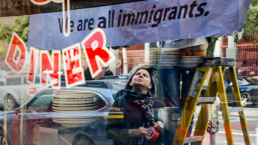 """After closing their restaurant for the day, Monica May watches while her partner Kristen Trattner hung a sign above their Nickel Diner in Downtown Los Angeles in solidarity with a national """"Day Without Immigrants."""""""