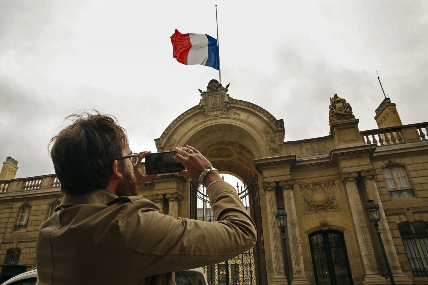 Sylvain Perriot stops to take a picture of the flag at half mast above the Presidential Palace in Paris. France's Sate of Emergency will continue, with flags at half mast.