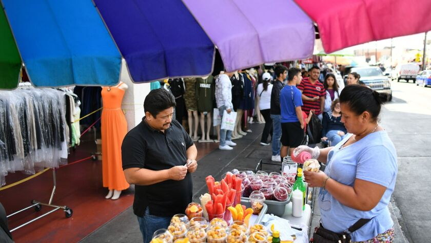 Sidewalk vendor Maria Franco sells food along Maple Avenue in the Fashion District in downtown Los Angeles.