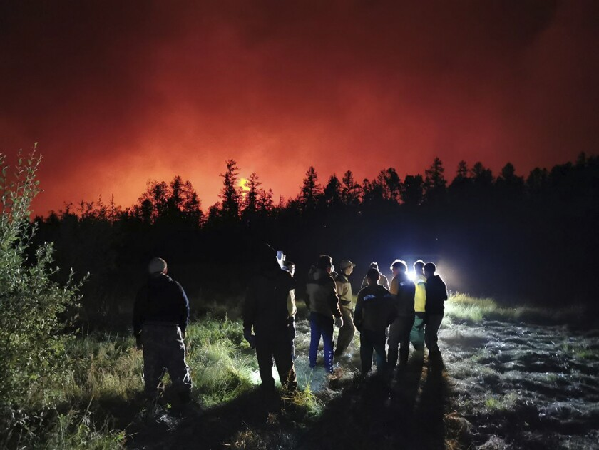Firefighters and volunteers have a briefing as they work at the scene of forest fire at Gorny Ulus area west of Yakutsk, in Russia, Saturday, Aug. 7, 2021. Wildfires in Russia's vast Siberia region endangered several villages Saturday and prompted authorities to evacuate residents of some areas. In northeastern Siberia, 93 active forest fires burned across 1.1 million hectares (2.8 million acres) of Sakha-Yakutia, officials said, making it the worst affected region of Russia. (AP Photo/Ivan Nikiforov)