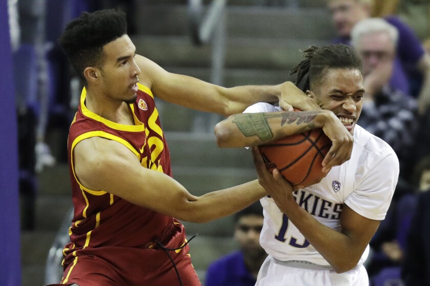 USC forward Isaiah Mobley, left, and Washington forward Hameir Wright battle for the ball during the Trojans' 72-40 loss Sunday.
