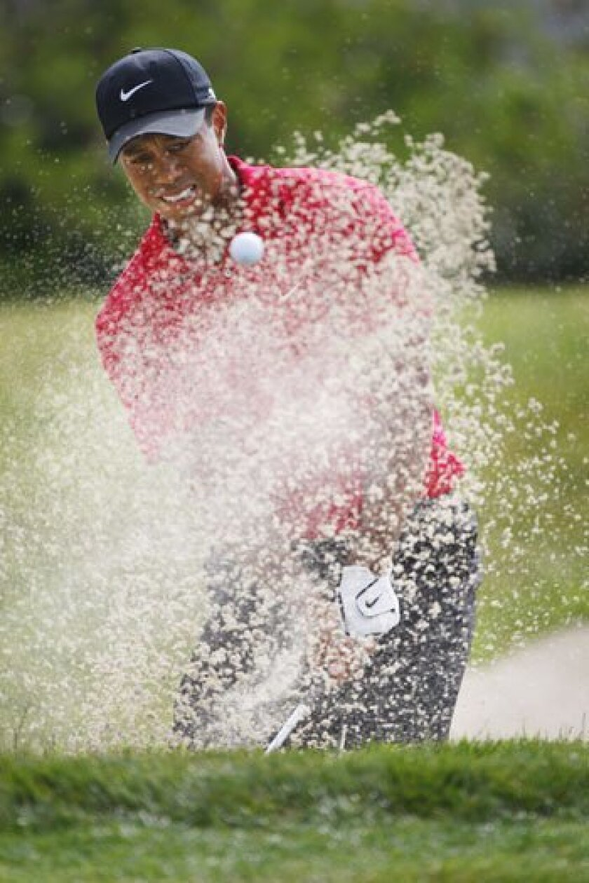 Tiger Woods hits out of the sand trap on the No. 7 hole. Each time he stumbled into trouble he managed to get out of it.